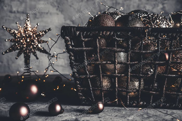 Wicker basket with Christmas toys and holiday decorations lights, copy space, new year decoration