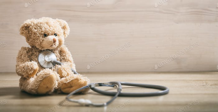 Teddy bear and a stethoscope on a wooden floor