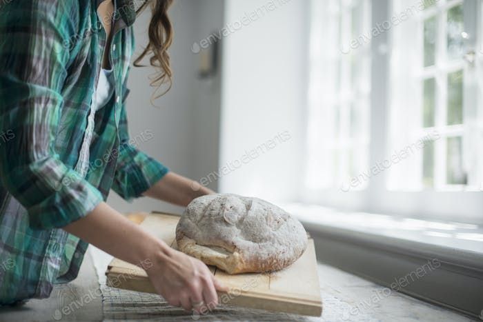 A family gathering. A woman carrying a fresh baked loaf of bread.