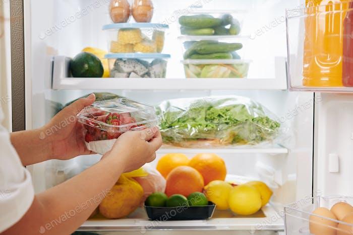 Woman putting strawberries in fridge