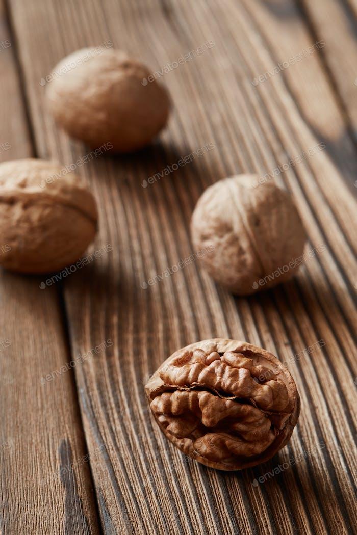 Walnuts and kernels on a dark rusty wood backdrop