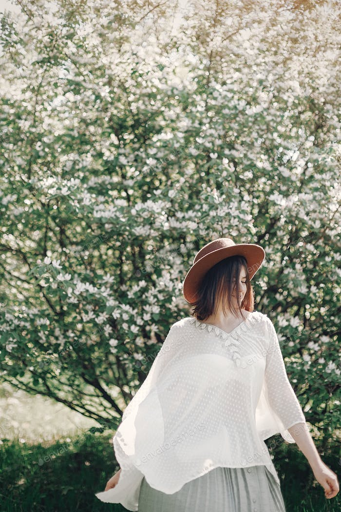 Sinnliches Porträt der schönen Hipster Frau im Hut riecht weiße Blumen im Frühling