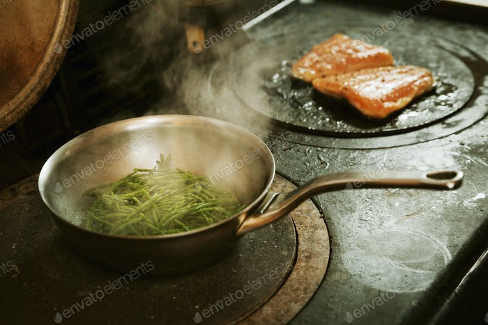 Frying pan with samphire and a fish fillet grilled on a stove.