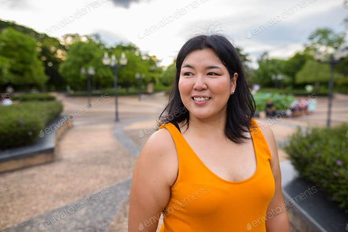 Beautiful overweight Asian woman thinking and smiling in park