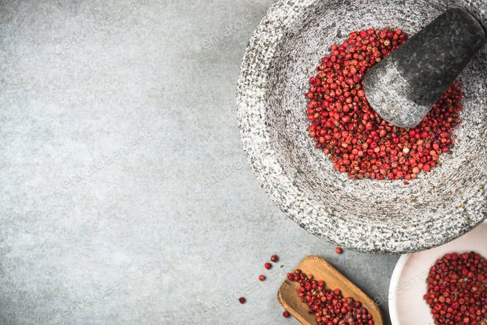Red peppercorn seed in granite mortar or pestle