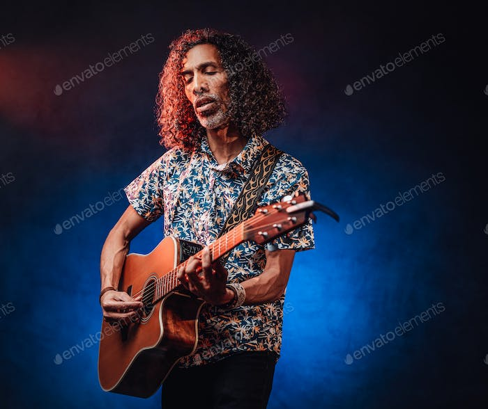 Talented hispanic musician in a hawaiian shirt playing guitar on a dark