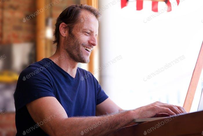 glücklicher Mann, der am Laptop arbeitet