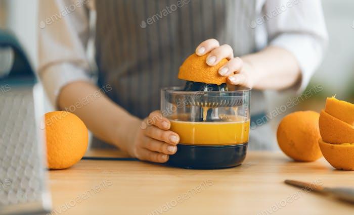 Frau bereitet frischen Orangensaft