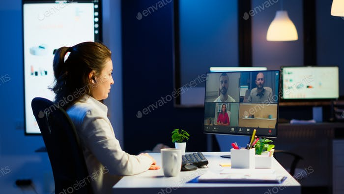 Businesswoman talking during video conference with team in midnight