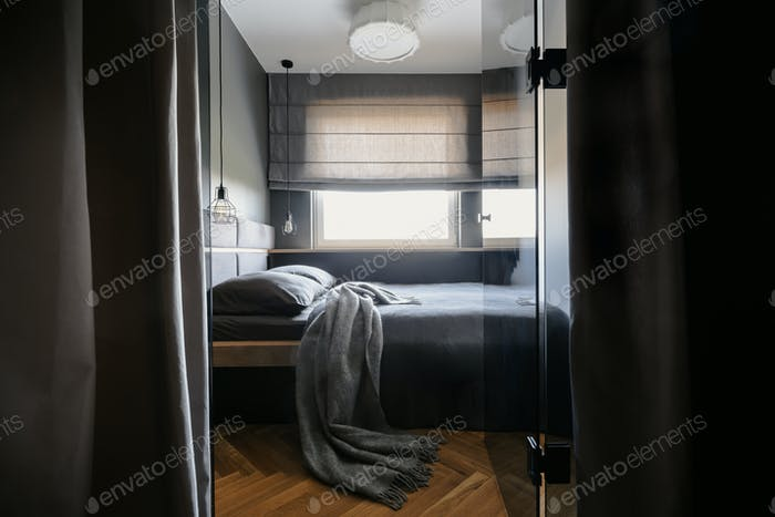 Grey blanket and pillows on bed in simple hotel bedroom interior