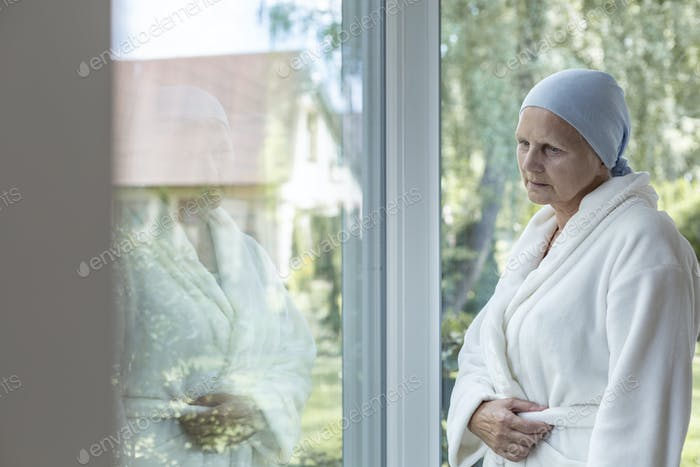 Lonely woman with cancer standing next to a window