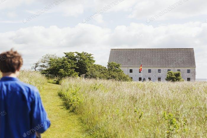 Rear view of man walking on grassy field leading towards barn against cloudy sky