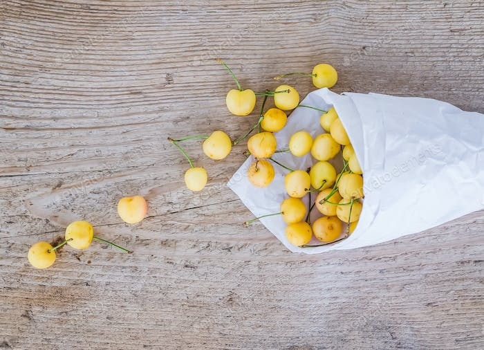 Yellow sweet-cherries in a paperbag on a rought wood surface