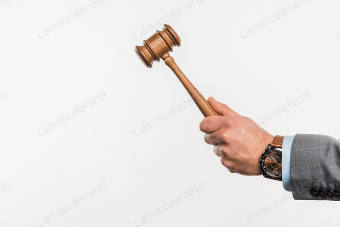 close-up partial view of male judge holding wooden hammer isolated on white
