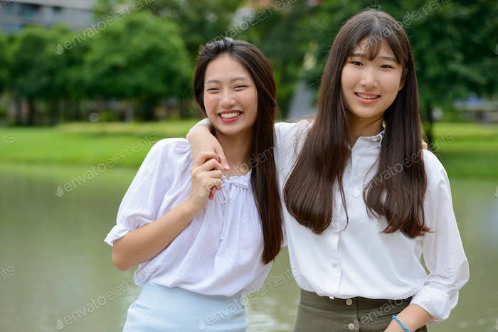 Two happy young beautiful Asian teenage girls bonding together at the park
