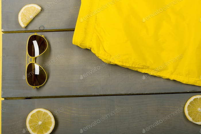 man beach accessories on wooden background. Yellow Swim Trunks, aviator sunglasses between parts