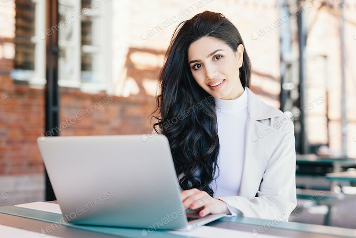 Successful European businesswoman with beautiful appearance working at a cafe on laptop