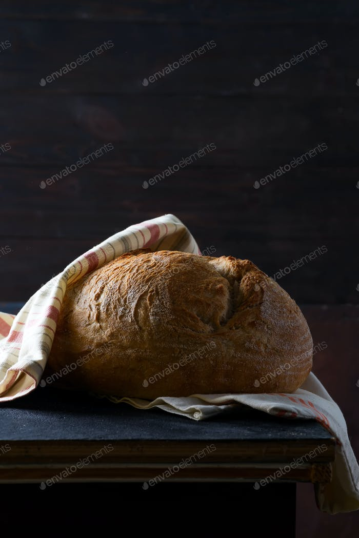 Homemade bread sourdough, rustic baked bread with a napkin on a dark background, copy space