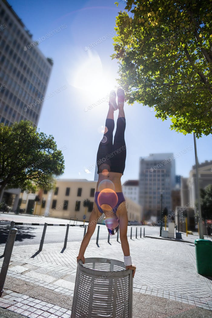 Athletic woman performing handstand on bin in the city