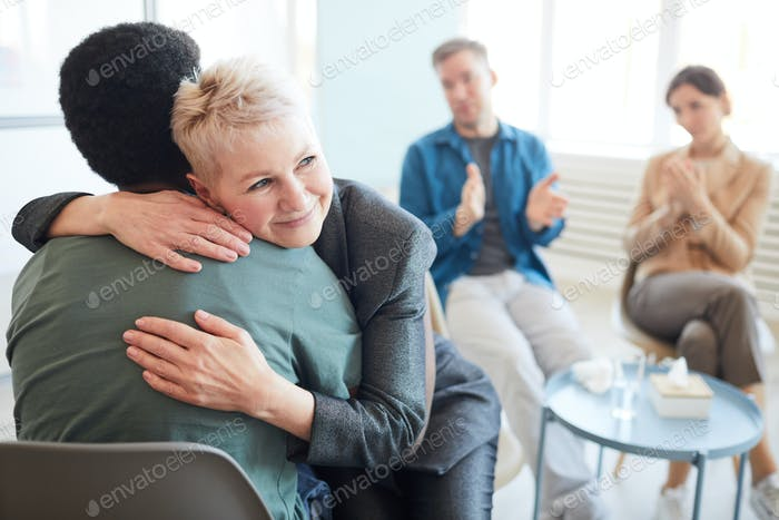 Mature Psychologist Embracing Patient in Support Group
