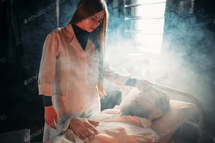 Wife sitting against ill husband in hospital bed