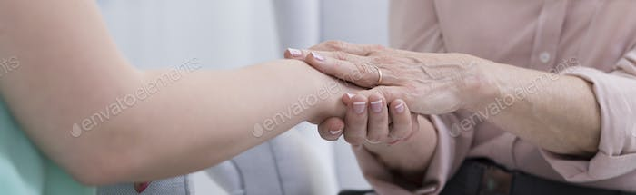 Doctor touches her patient' hand
