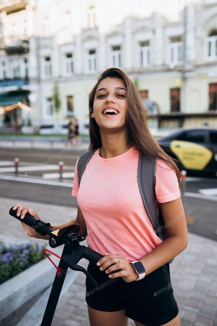 Placeit - Junge schöne Frau, die einen Elektro-Scooter reitet