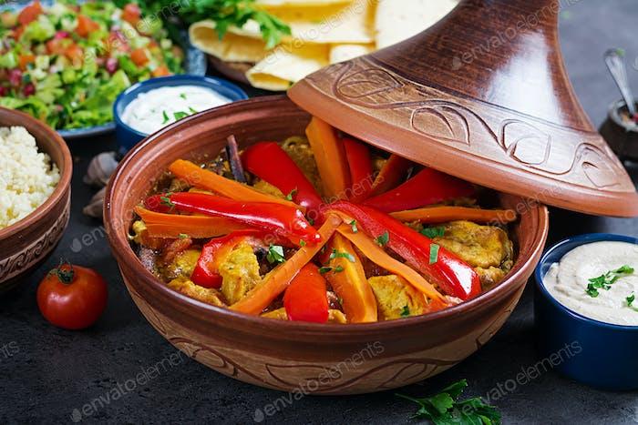 Marokkanisches Essen. Traditionelle Tajine Gerichte, Couscous und frischer Salat auf rustikalem Holztisch.