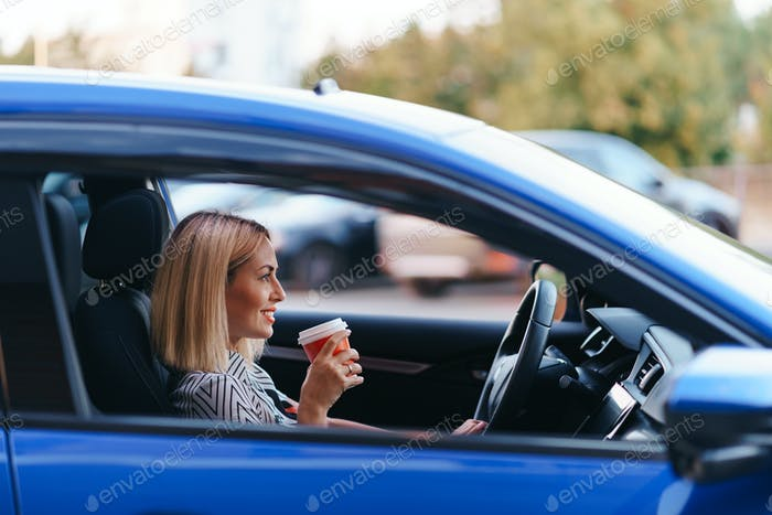 Lovely woman driving satisfied with coffee to go
