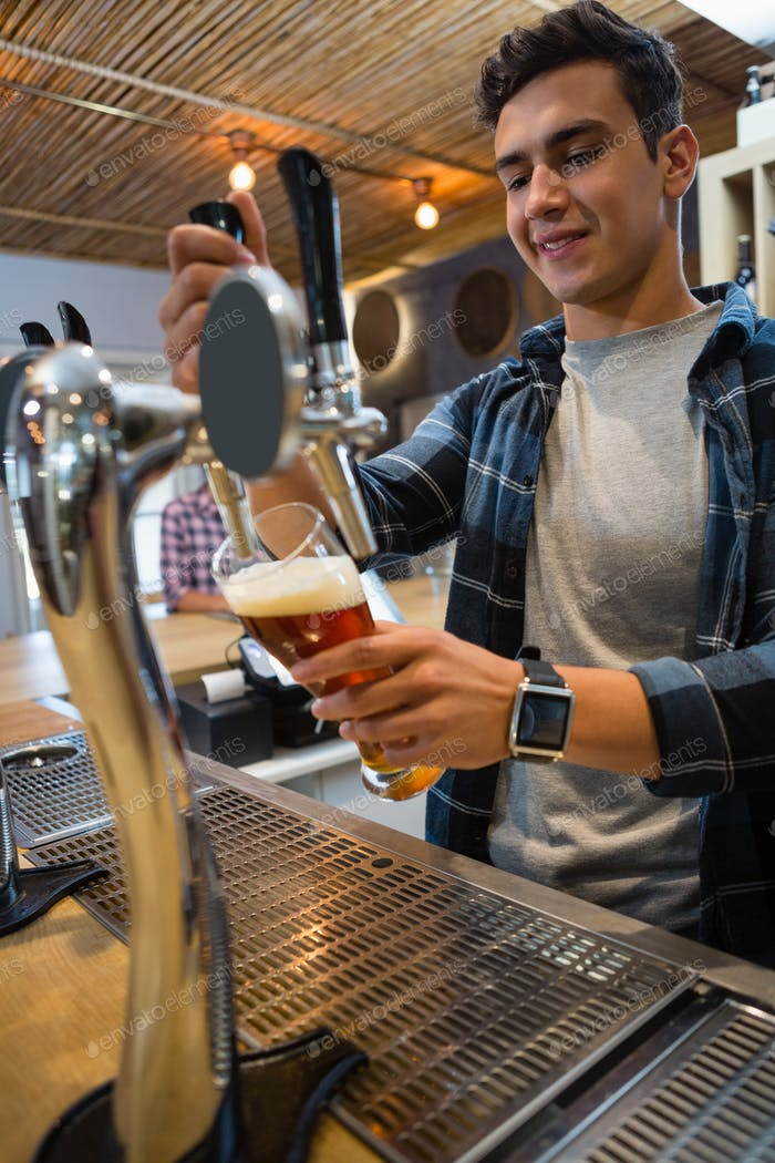 Bartender pouring beer from tap in glass