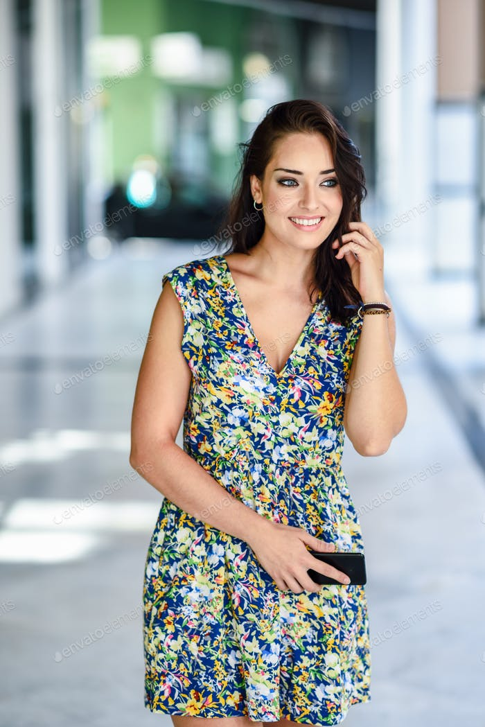 Young woman walking on the street carrying smart phone.