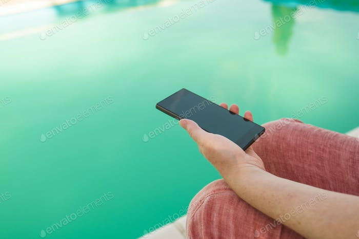 Woman with mobile phone by the swimming pool