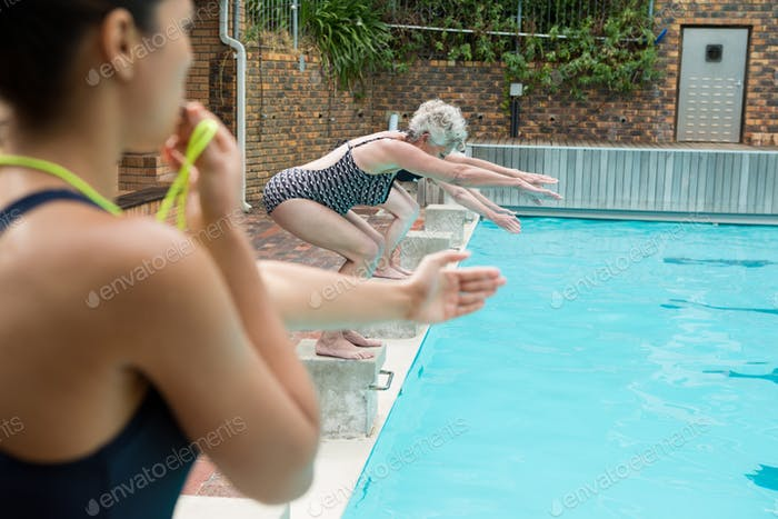 Female trainer whistling while senior women diving into pool