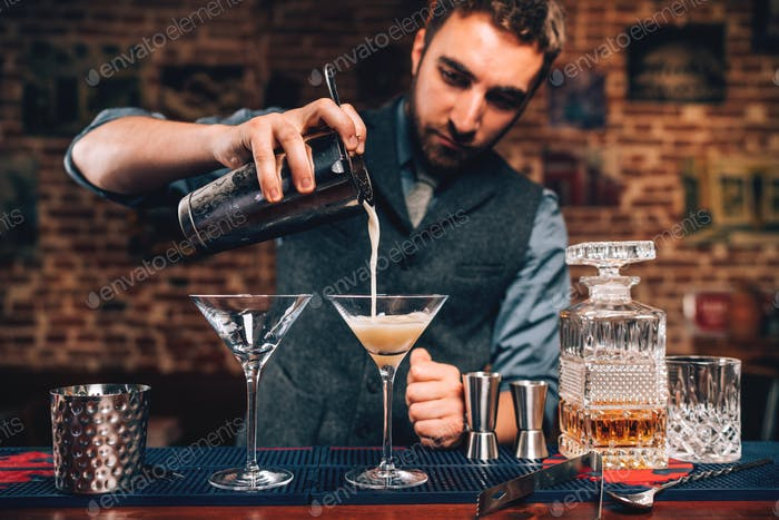 barman pouring fancy cocktail in bar at party. Manhattan cocktail beverage in nightclub