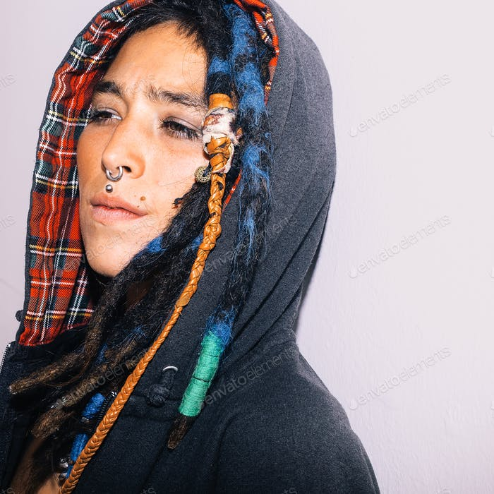 Portrait of Latin girl with dreadlocks and piercing. Street fash