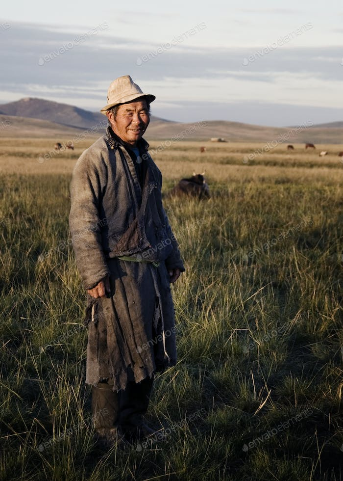 Mongolian Milking Man Standing In A Scenic View Of The Field