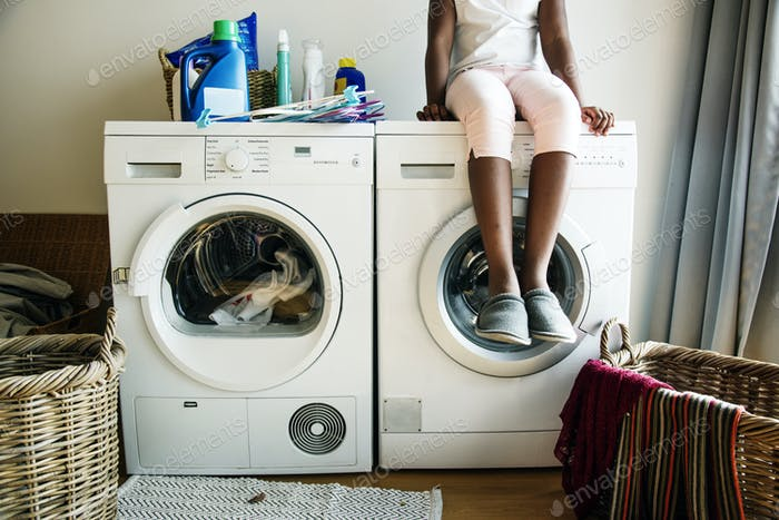 Young teen girl waiting for clothe to be washed from washing machine