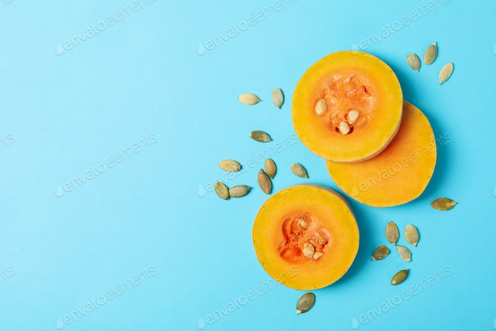 Squash slices and seeds on blue background, space for text