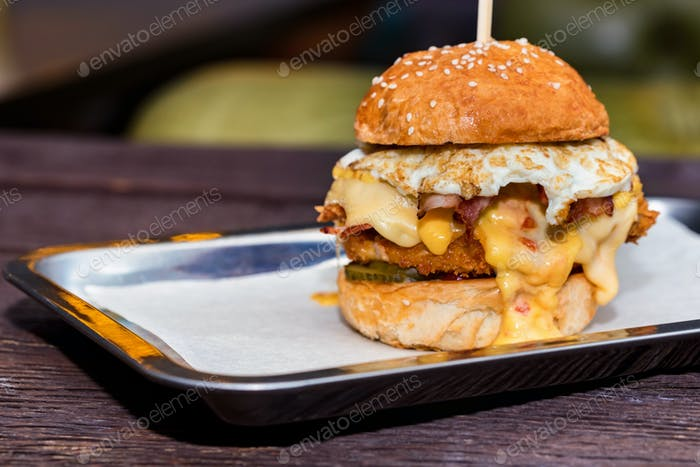 Close up tall tasty burger with cheese and egg served on tray