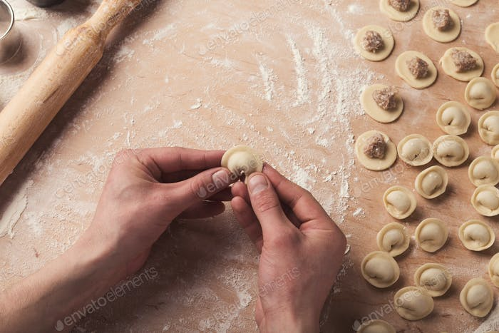 Preparing dumplings with meat, forming small ravioli