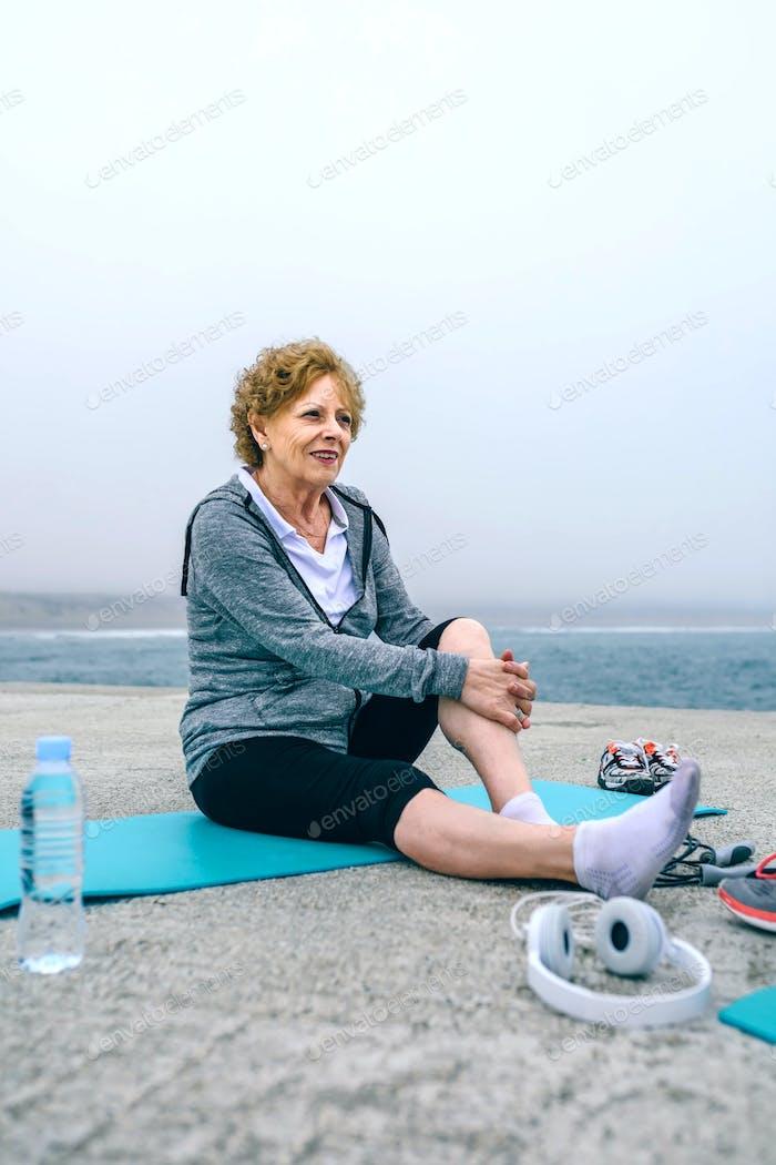 Deportista senior relajarse en esterilla de yoga