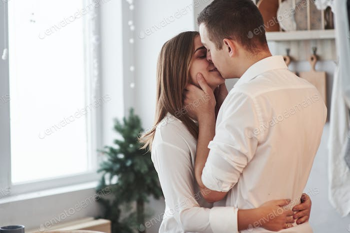 Happy couple kissing in the kitchen. Having nice weekend together