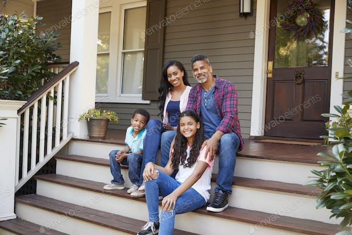 Familie mit Kindern sitzen auf Stufen, die bis zur Veranda des Hauses