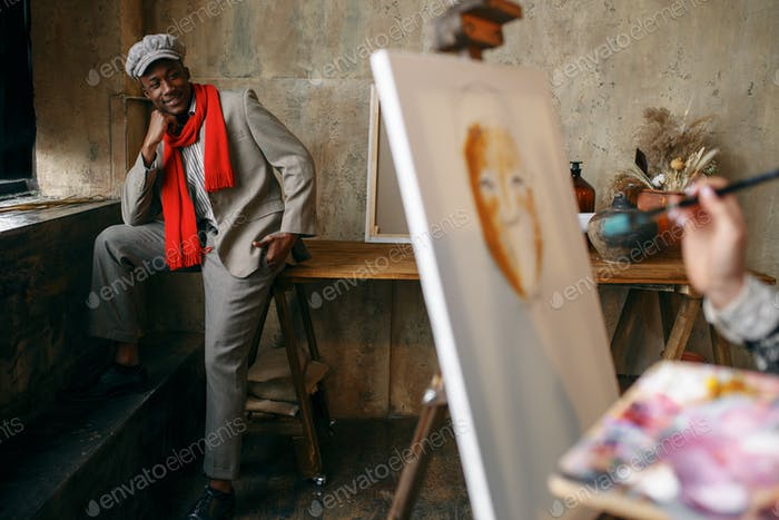 Female painter with brush draws male model