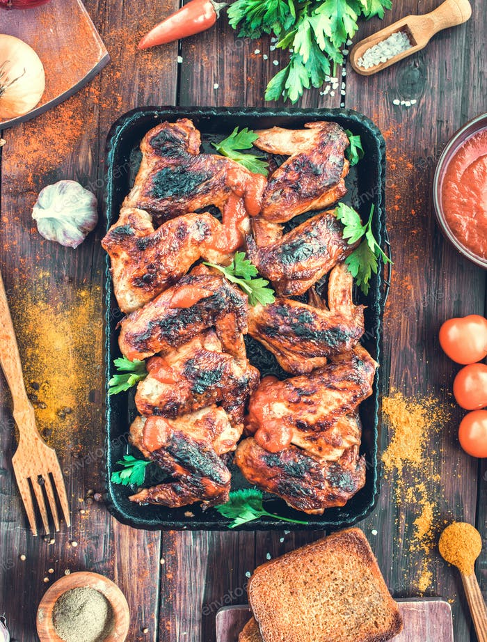 Grilled spicy chicken wings on serving pan