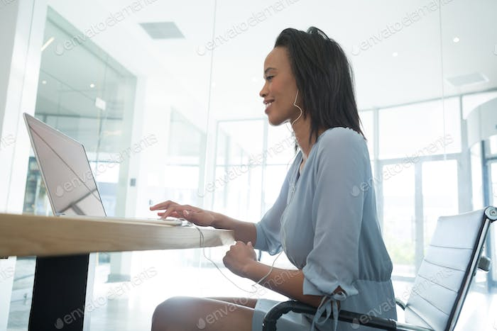 Female executive listening music while using laptop at desk