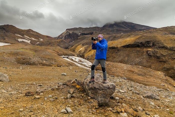 Joven fotógrafo en el Fondo de rocas volcánicas. Kamchatk