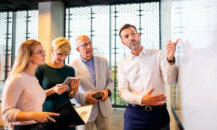 Деловые люди перед белой доской копировальной площадкой дают презентационный отчет в конференц-зале