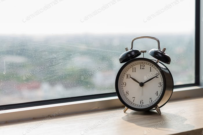 Vintage alarm clock at windows at morning
