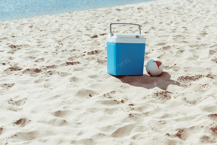 blue cooler box and volleyball ball on sandy beach